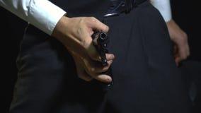 Человек в костюме имеет повороты потехи его шляпа на оружие перед его брюками мухы акции видеоматериалы