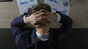 Человек в костюме полагаясь над столом офиса и кладя руки на голову, отчаяние, стресс сток-видео
