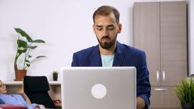 Человек в костюме работает на компьютере пока женщина смотрит ТВ на заднем плане видеоматериал