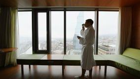 Человек в кофе купального халата выпивая в утре, протягивающ и смотрящ городской пейзаж пока на командировке оставаясь внутри сток-видео