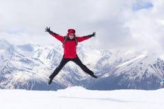 Человек в красной куртке на заднем плане снежных гор, человека Стоковая Фотография