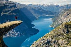 Человек в красной куртке скача на утес Trolltunga с голубым озером 700 метров более низко и интересного небо с облаками стоковая фотография rf