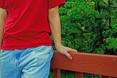 Человек в красной рубашке сидя на перилах стоковое фото rf