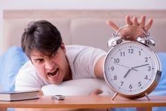 Человек в кровати расстроил страдать от инсомнии с cloc сигнала тревоги Стоковые Фото