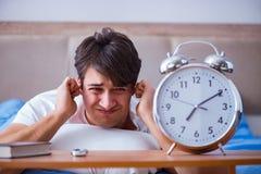 Человек в кровати расстроил страдать от инсомнии с cloc сигнала тревоги Стоковое Изображение