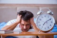 Человек в кровати расстроил страдать от инсомнии с cloc сигнала тревоги Стоковое Фото