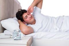 Человек в кровати страдая от инсомнии Стоковые Изображения RF