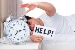Человек в кровати страдая от инсомнии Стоковые Изображения