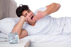 Человек в кровати страдая от инсомнии Стоковое Изображение