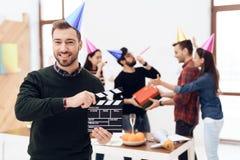 Человек в крышке держит clapperboard кино Стоковые Фото