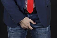 Человек в куртке пунша и галстуке владения бизнесмена на пахе, черной предпосылке стоковая фотография rf
