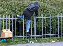 Человек в куртке с клобуком взбирается над загородкой стоковое изображение