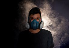 Человек в маске противогаза курит, черная предпосылка стоковое фото