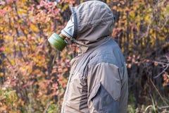 Человек в маске противогаза на предпосылке желтых красных листьев падает, защитный костюм Стоковые Изображения