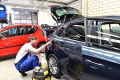 Человек в мастерской очищая автомобильное обслуживание для клиента Стоковые Фотографии RF