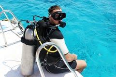 Человек в мокрой одежде, с aqualung, маской и воздушным шаром Водолаз в водолазном снаряжении подготавливает нырнуть стоковые фото
