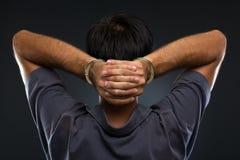Человек в наручниках на серой предпосылке Стоковая Фотография
