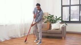 Человек в наушниках с веником очищая дома акции видеоматериалы