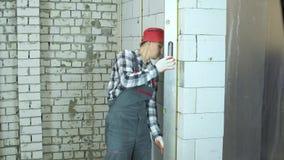 Человек в носке работы и красной крышке использует правителя конструкции для проверки качества стены видеоматериал