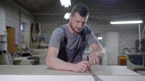 Человек в общем положении в панели гаража измеряя с вкладышем металла акции видеоматериалы