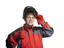Человек в одеждах деятельности и маске сварщика показывает большой палец руки и улыбки стоковая фотография