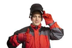 Человек в одеждах деятельности и маске сварщика показывает большой палец руки и улыбки стоковая фотография rf