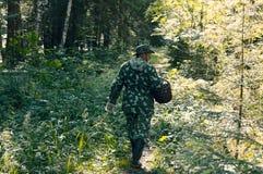 Человек в одеждах камуфлирования с корзиной стоковая фотография