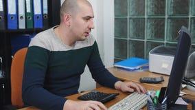 Человек в офисе работая на компьютере, говорящ по телефону и рассматривает использовать калькулятор сток-видео