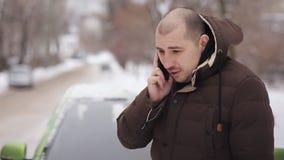 Человек в пальто зимы стоит около сломанном вниз с автомобиля и вызывает для помощи сток-видео