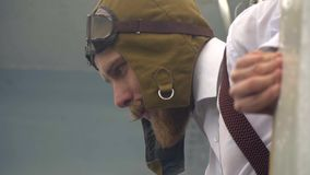 Человек в пилотном костюме ` s с шлемом на его голове peeking из самолета сток-видео