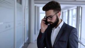 Человек в положении здания дела современном и talkin на телефоне сток-видео