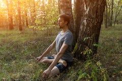 Человек в представлении лотоса размышляя outdoors природа в солнечном свете стоковые фотографии rf