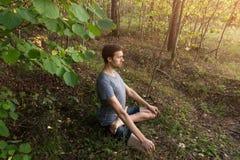 Человек в представлении лотоса размышляя outdoors в природе леса стоковые фото