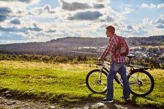 Человек в природе с велосипедом на предпосылке гор и голубого неба стоковые фотографии rf