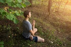 Человек в раздумье представления лотоса, молитве, йоге, outdoors в природе стоковое фото rf