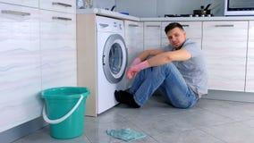 Человек в резиновых перчатках имеет остатки от чистки сидя на поле кухни сток-видео