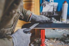 Человек в ремонтнике рабочей одежды в обслуживании лыжи мастерской ремонтируя сползая поверхность лыж В руках аппаратуры, b стоковая фотография rf