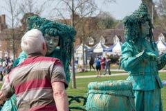 Человек в рубашке stripey целует женщину в зеленом цвете одетую как ведьма Стоковые Изображения RF