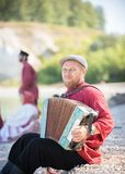 Человек в русской национальной стойке костюма на предпосылке изумительного ландшафта играя аккордеон стоковые фото