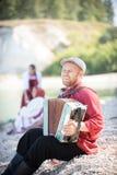 Человек в русской национальной стойке костюма на предпосылке изумительного ландшафта играя аккордеон, усмехаясь стоковая фотография