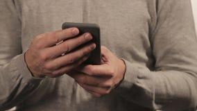 Человек в свитере беседуя по телефону на белой предпосылке Люди и communoication видеоматериал