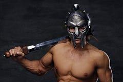 Человек в серебряном шлеме гладиатора держит железную шпагу Стоковое Изображение