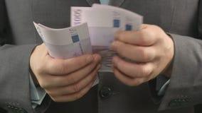 Человек в сером костюме подсчитывая евро, конец вверх рук бизнесмена держа наличные деньги сток-видео