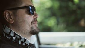 Человек в солнечных очках управляет автомобилем видеоматериал