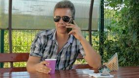 Человек в стеклах в газебо говоря по телефону, есть сэндвич кофе видеоматериал