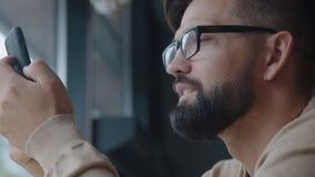 Человек в стеклах держит телефон перед стороной и смотрит экран сток-видео