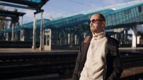 Человек в стеклах стоит на платформе железнодорожного вокзала и ожидания прибытия поезда акции видеоматериалы