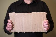 Человек в темной рубашке держа часть картона Подготовленный для вашего текста стоковая фотография