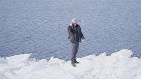 Человек в теплом положении пальто и шляпы на краю ледника принимая selfie Изумляя природа снежного ледника _ сток-видео