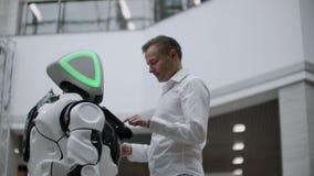 Человек в торговом центре связывает с советником робота Современный продавец магазина и робота Робот помогает человеку в видеоматериал